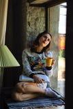Девушка мечтая окном Стоковые Изображения