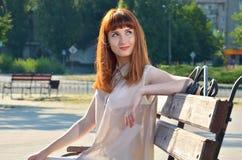 Девушка мечтая сидеть на стенде Стоковые Фото
