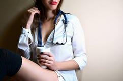 Девушка медсестры детенышей сидя с кофейной чашкой Стоковые Изображения
