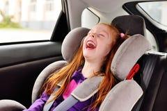 Девушка младенца маленькая рыжеволосая усмехаясь пока сидящ в автокресле ребенка стоковое изображение rf