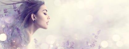 Девушка модели красоты с цветками лаванды Красивая молодая женщина брюнета с портретом профиля волос летания длинным стоковое изображение