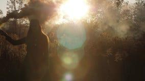 Девушка моды идя в пирофакелы нося дыма поля выпуская облака желтого дыма 4K медленного Mo видеоматериал