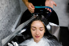 Девушка моет ее голову в салоне красоты Расцветка волос, фольга стоковое изображение