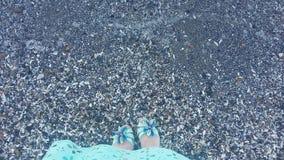 Девушка морем, ноги ` s девушки около воды Стоковая Фотография RF
