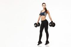 Девушка молодого фитнеса sporty в наушниках тренируя держащ гантели над белой предпосылкой Стоковое фото RF