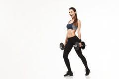 Девушка молодого фитнеса sporty в наушниках тренируя держащ гантели над белой предпосылкой Стоковая Фотография