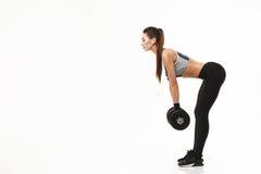 Девушка молодого фитнеса sporty в наушниках тренируя держащ гантели над белой предпосылкой Стоковое Фото