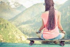 Девушка моды битника делая йогу, ослабляя на скейтборде на горе Стоковые Изображения