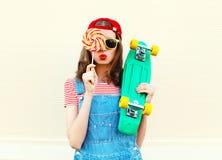 Девушка моды портрета довольно холодная с леденцом на палочке и скейтбордом над белизной Стоковое фото RF