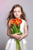 Девушка моды рыжеволосая с тюльпанами в руках Фото студии на предпосылке покрашенной светом День рождения, праздник, день ` s мат Стоковое Изображение RF