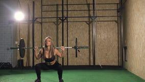 Девушка мышечного молодого фитнеса красивая белокурая поднимая крест веса приспособленный в спортзал сток-видео