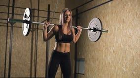Девушка мышечного молодого фитнеса красивая белокурая поднимая крест веса приспособленный в спортзал акции видеоматериалы