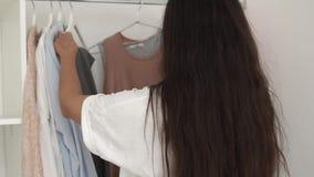 Девушка наблюдает ее одежды на шкафе в комнате и решает чего нести утро сток-видео