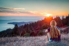 Девушка наблюдает заход солнца Стоковые Изображения RF