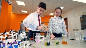 Девушка наблюдает химикаты мальчика смешивая акции видеоматериалы