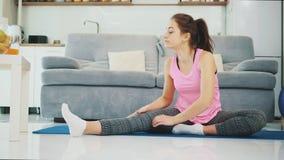 Девушка наслаждается фитнесом дома пока усмехающся акции видеоматериалы
