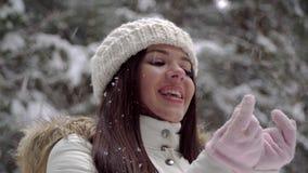 Девушка наслаждаться снежности в девушке леса зимы красивой с длинными темными волосами в белой куртке идя в передние части зимы сток-видео