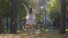 Девушка наслаждаясь выходными в парке путем выбирать вверх листья осени от земли и бросать их в воздухе видеоматериал