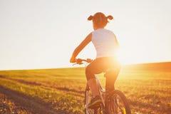Девушка наслаждаясь ездой велосипеда на заходе солнца Стоковые Изображения