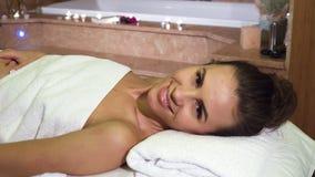 Девушка наслаждаясь обработками курорта смотрит в камеру и улыбки стоковая фотография rf