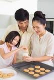 Девушка наслаждаясь печеньями и молоком с родителями в кухне Стоковая Фотография RF