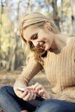 Девушка наслаждаясь радиотелеграфом интернета на smartphone в n Стоковое фото RF