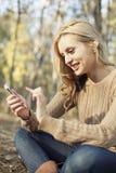 Девушка наслаждаясь радиотелеграфом интернета на smartphone в n Стоковое Изображение RF