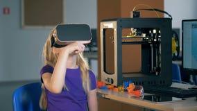 Девушка начальной школы используя стекла виртуальной реальности исследуя виртуальную реальность 3D в школьном классе