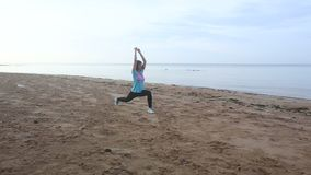 девушка начинает сделать тренировки утра на пляже на восходе солнца видеоматериал