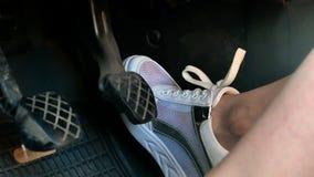 Девушка на белизне хихикает ботинки отжимая педали 4k автомобиля видеоматериал