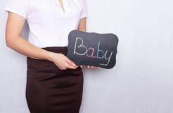Девушка на белой предпосылке держа знак с младенцем надписи, женскую неплодородность, космос экземпляра, рождаемость стоковая фотография rf