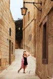 Девушка на ботинках pointe в танцах платья принцессы идет в узкие улицы древнего города стоковые фотографии rf