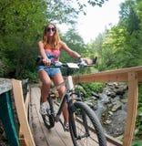 Девушка на велосипеде пересекая деревянный мост над рекой горы Стоковое фото RF