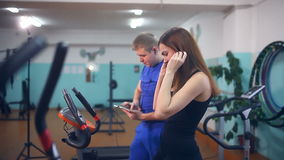 Девушка на велотренажере и человеке с доской сзажимом для бумаги в спортзале сток-видео