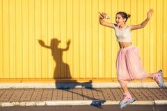 Девушка на желтой предпосылке стены стоковые изображения rf