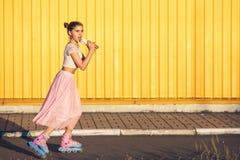 Девушка на желтой предпосылке стены стоковая фотография rf