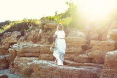 Девушка на заходе солнца в ярких лучах, в платье представляя на скалистом пляже на предпосылке захода солнца Она касается ее воло стоковые фотографии rf