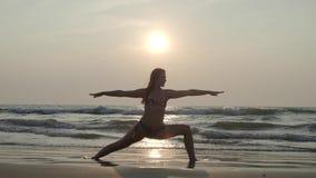 Девушка на заходе солнца морем приниманнсяая за йога 4K видеоматериал