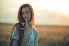 Девушка на заходе солнца в поле Стоковая Фотография