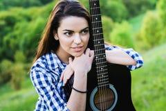 Девушка на зеленом луге играя гитару Стоковая Фотография RF