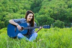 Девушка на зеленом луге играя гитару Стоковое фото RF