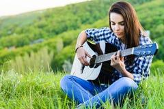 Девушка на зеленом луге играя гитару Стоковое Изображение RF
