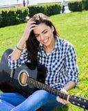 Девушка на зеленом луге играя гитару Стоковые Изображения RF