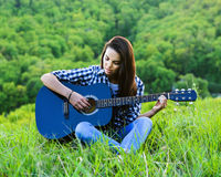Девушка на зеленом луге играя гитару Стоковые Фото