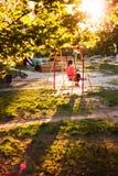 Девушка на качании в спортивной площадке Стоковые Изображения