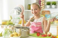 Девушка на кашеваре кухни стоковая фотография rf