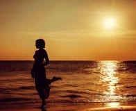 Девушка на красивом пляже во время захода солнца Стоковые Фото