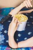 Девушка на кресле смотря ТВ и есть попкорн Стоковое Изображение