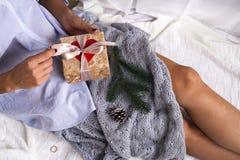 Девушка на кровати держит подарок стоковые фотографии rf