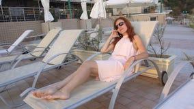 Девушка на курорте морем и бассейном говоря на телефоне видеоматериал